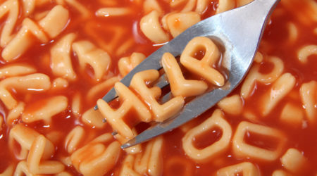 Spaghetti letter spelling the word help with the letters held up on a fork.