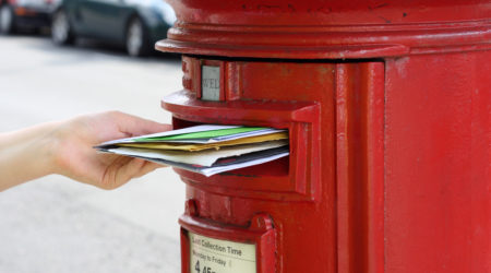 girls hand posting letters to red british postbox on street